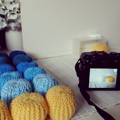 Group of dolls' house modern miniature pouffes, next to a miniature room setup and a camera ready to photograph it.
