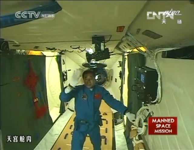 Chỉ huy trưởng Cảnh Hải Bằng của sứ mệnh Thần Châu 9 đang vẫy tay chào trước ống kính từ trạm Thiên Cung 1 sau sự ghép nối thành công giữa tàu và trạm vũ trụ vào ngày 18 tháng 6 năm 2012. Đây là sứ mệnh có người lái đầu tiên của Trung Quốc lên quỹ đạo Trái Đất và hình ảnh này được truyền hình trực tiếp trên các kênh truyền hình quốc gia Trung Quốc. Hình ảnh: CNTV/CCTV.