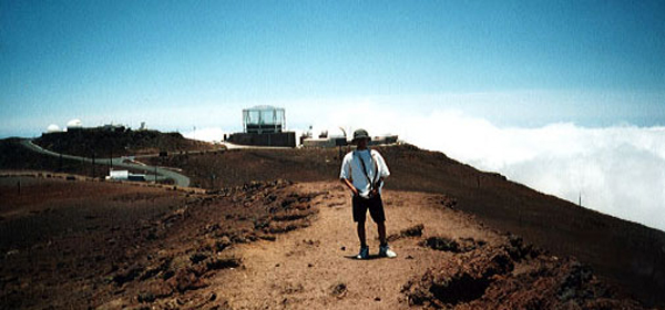Posing with a U.S. Air Force observatory behind me on the Haleakala volcanic summit.