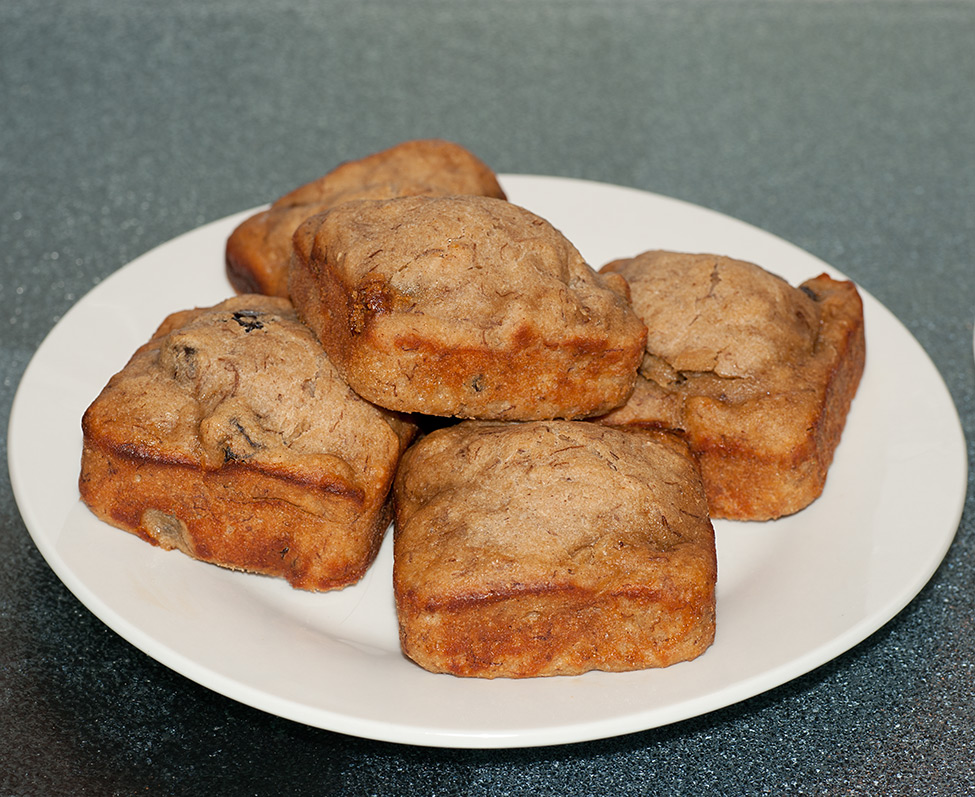 A plate of square banana apple muffins with raisins and nuts.