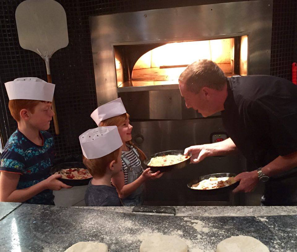 Pizza Making at Babucho Newcastle | Children's Menu & Lunch Review - handing the chef our pizzas for the pizza oven