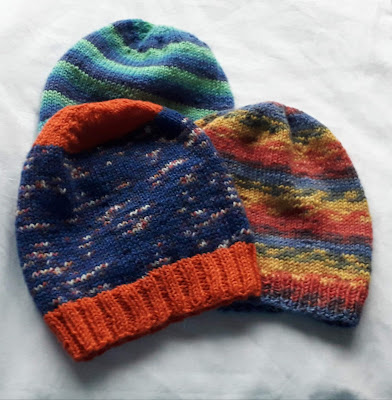 Three hand knitted hats - one in blue and turquoise stripes, one with an orange brim blue hat and the third is mottled red, yellow and blue stripes.
