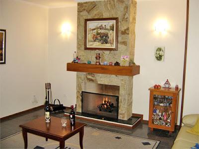 Sala de estar praticamente pronto com a lareira de pedra, o roda pé de madeira e com massa mão única desempenada e filtrada pintada e já com os móveis no lugar.