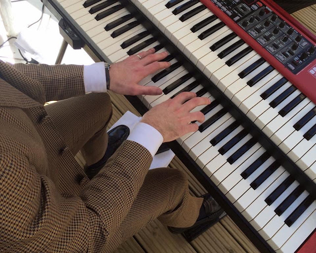 Man in suit playing Nord Electro 5D keyboard at outdoor British wedding Close up of hands on keys