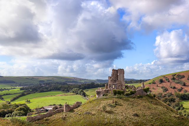 Billowy clouds move over the atmospheric ruins of Corfe Castle in Dorset