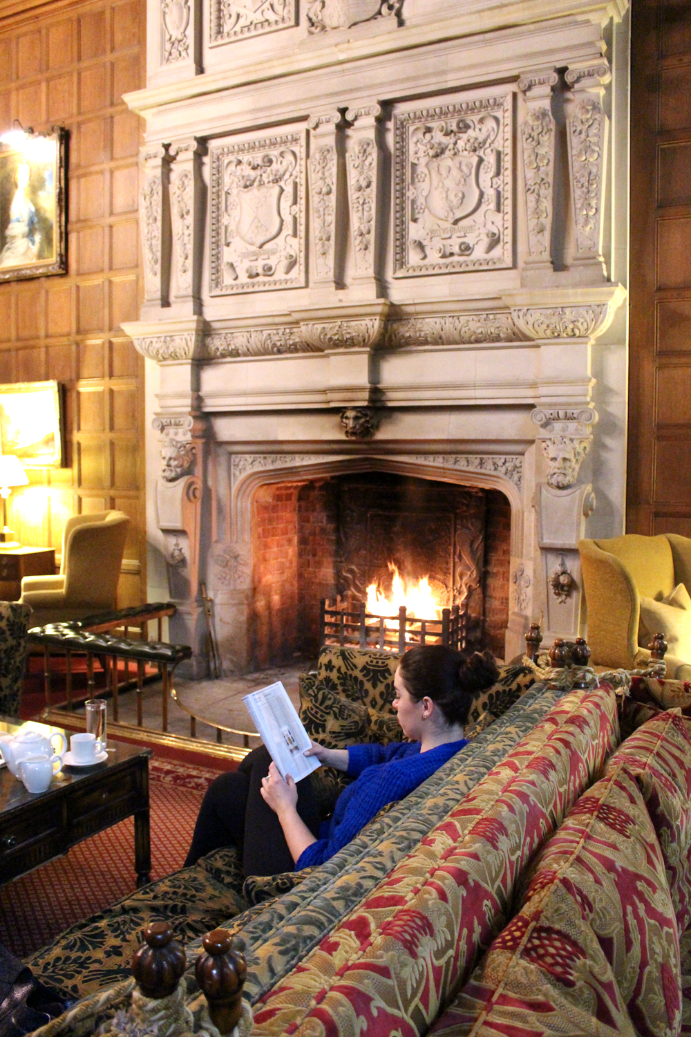 Reading by the fire at Rushton Hall, Northamptonshire - UK luxury travel blog