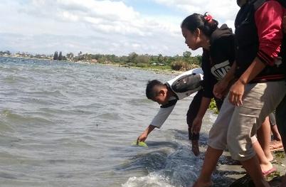 Teman-teman korban menaruh sirih ke dalam air sebagai lambang permohonan kepada penghuni Danau Toba agar Oci dimunculkan.
