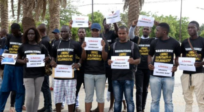 Anti-slavery activists demonstrate in Dakar against the imprisonement of fellow activists in Mauritania, holding cards with the names of those detained. By Seyllou