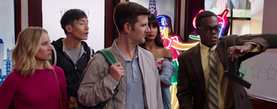 From left: Eleanor, Jason, Trevor, and Tahani all look at Chidi, who is holding the base of a gun between his thumb and forefinger