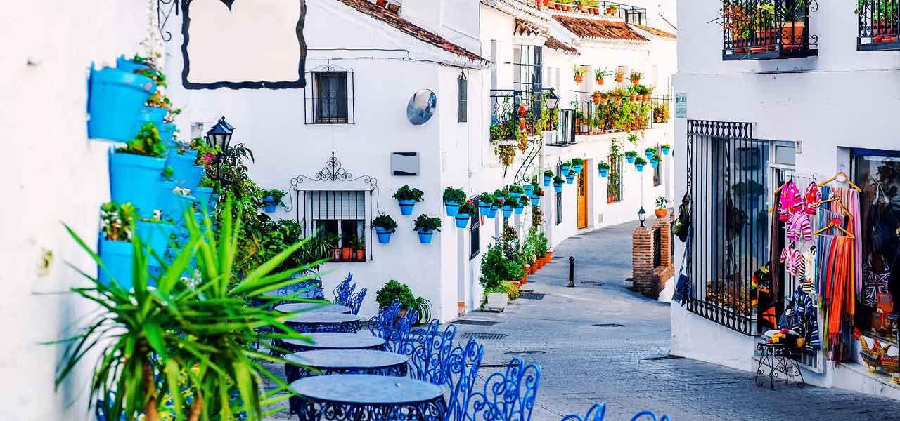 decoración patio andaluz blanco con macetas azules colgadas de la pared y mesas de forja