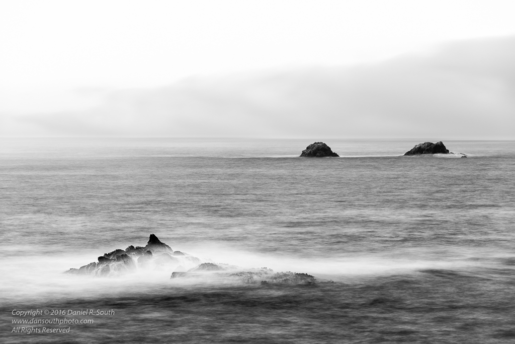 a photo in black and white of waves and rocks in the pacific ocean