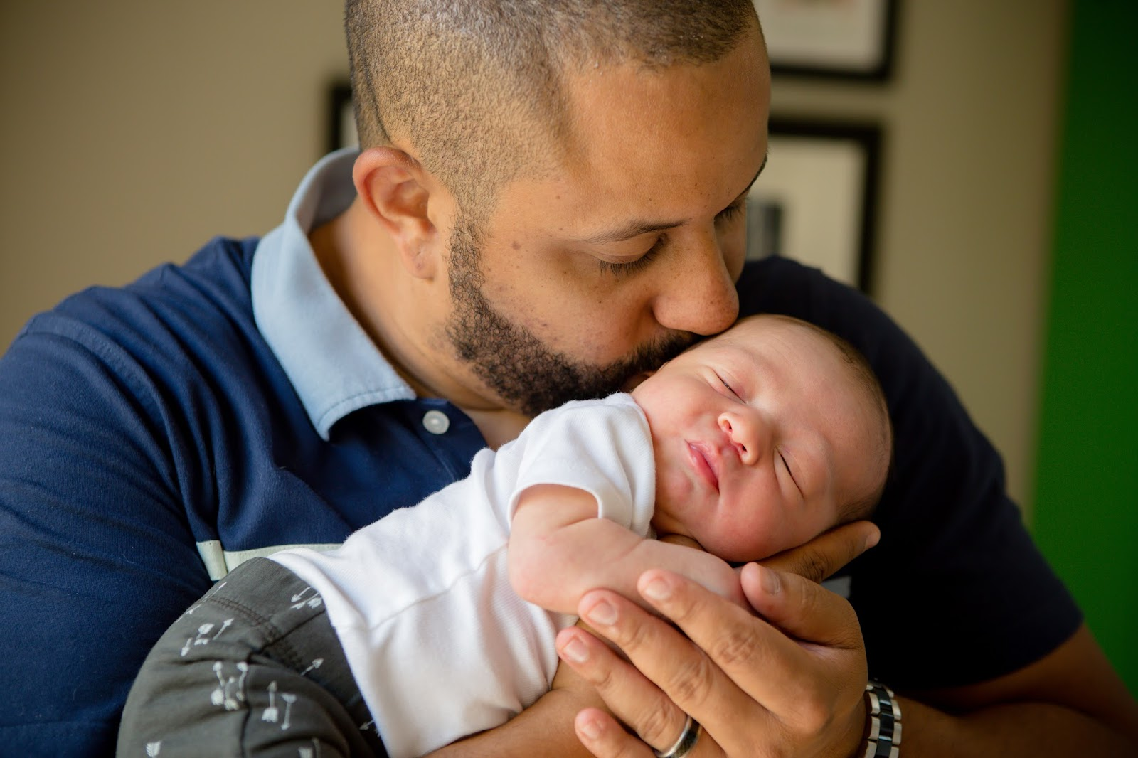 newborn baby with dad kissing
