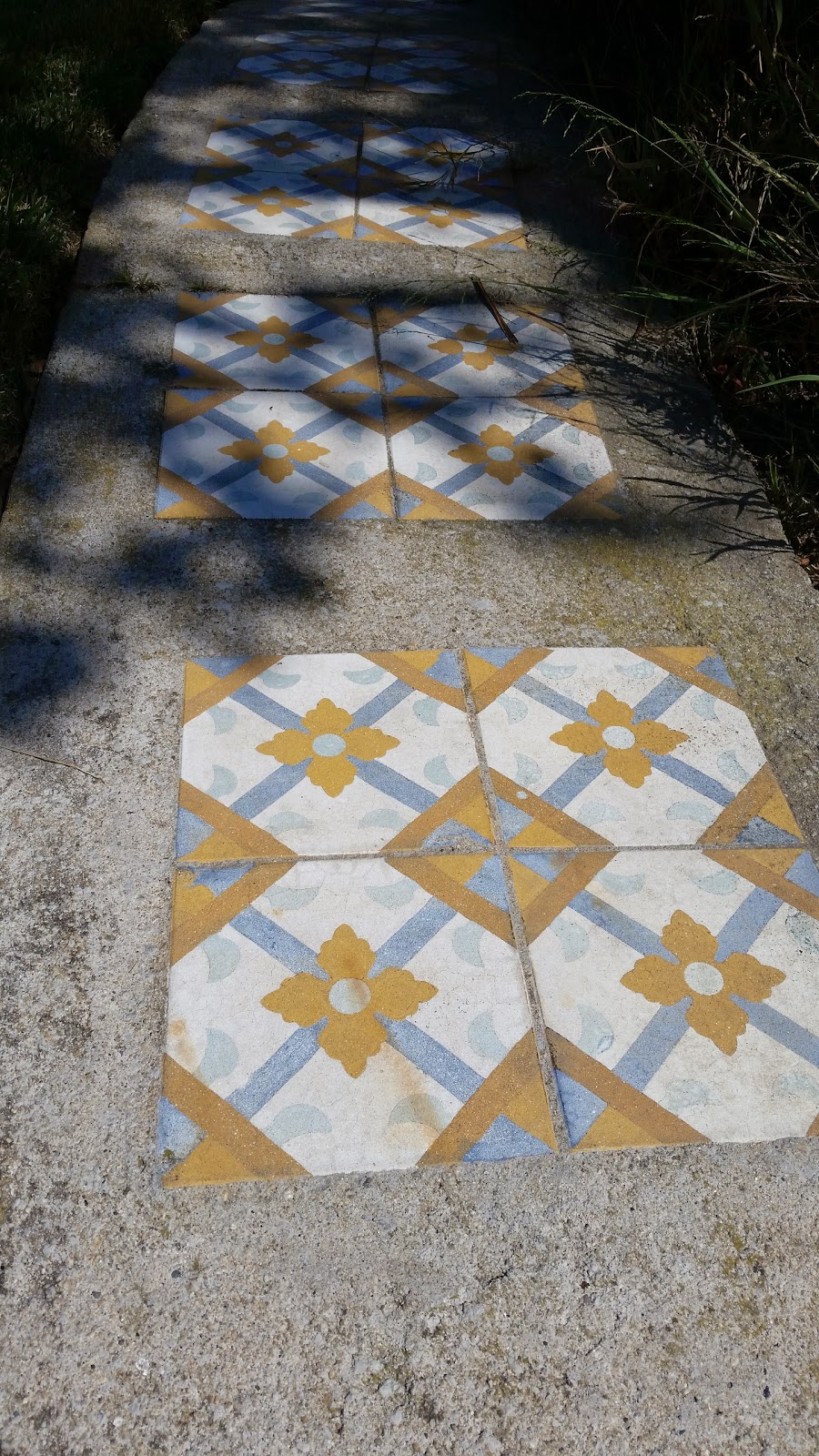 Patterned cement tile placed in a poured cement walkway