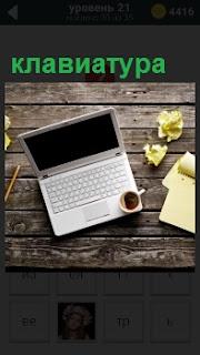 На столе лежит ноутбук с клавиатурой, на которой стоит чашка с кофе и рядом записи в тетради