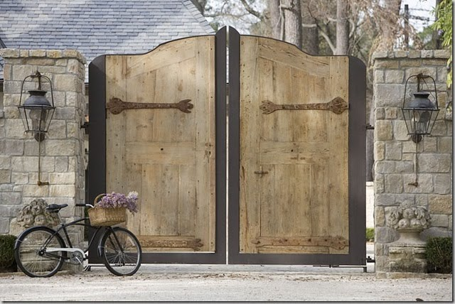 Breathtaking and massive wood doors and charming bicycle at entrance of European inspired home (found on Hello Lovely)