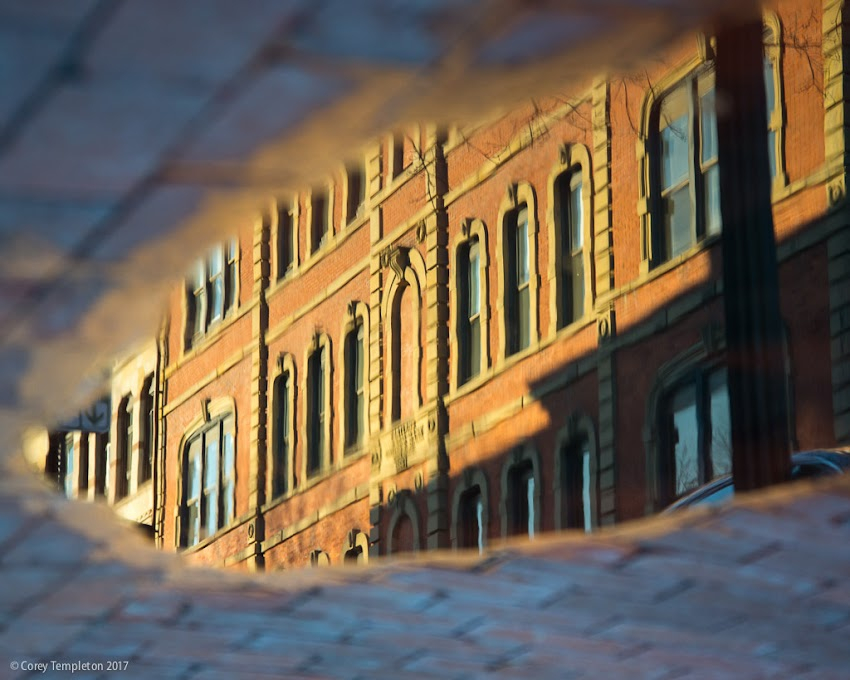 Portland, Maine USA April 2017 photo by Corey Templeton. A sidewalk reflection of part of the Portland Savings Bank Building on Exchange Street.