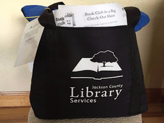 Book bag with Jackson County Library Services logo in it. The bag is stuffed full and a paper is visible from the neck of the bag. The paper reads, 'Book Club in a Bag Check-Out Sheet'