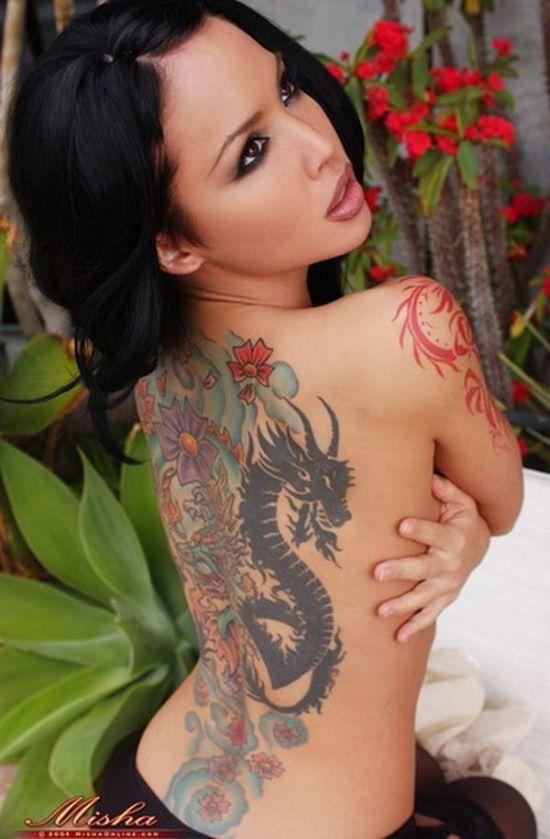 Chica asiática de espaldas, vemos en su espalda un tatuaje de dragón a tamaño total,