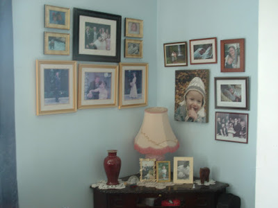 Many family photos, both on a wall and a table
