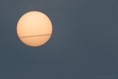 Sol, mancha solar y estela de avión