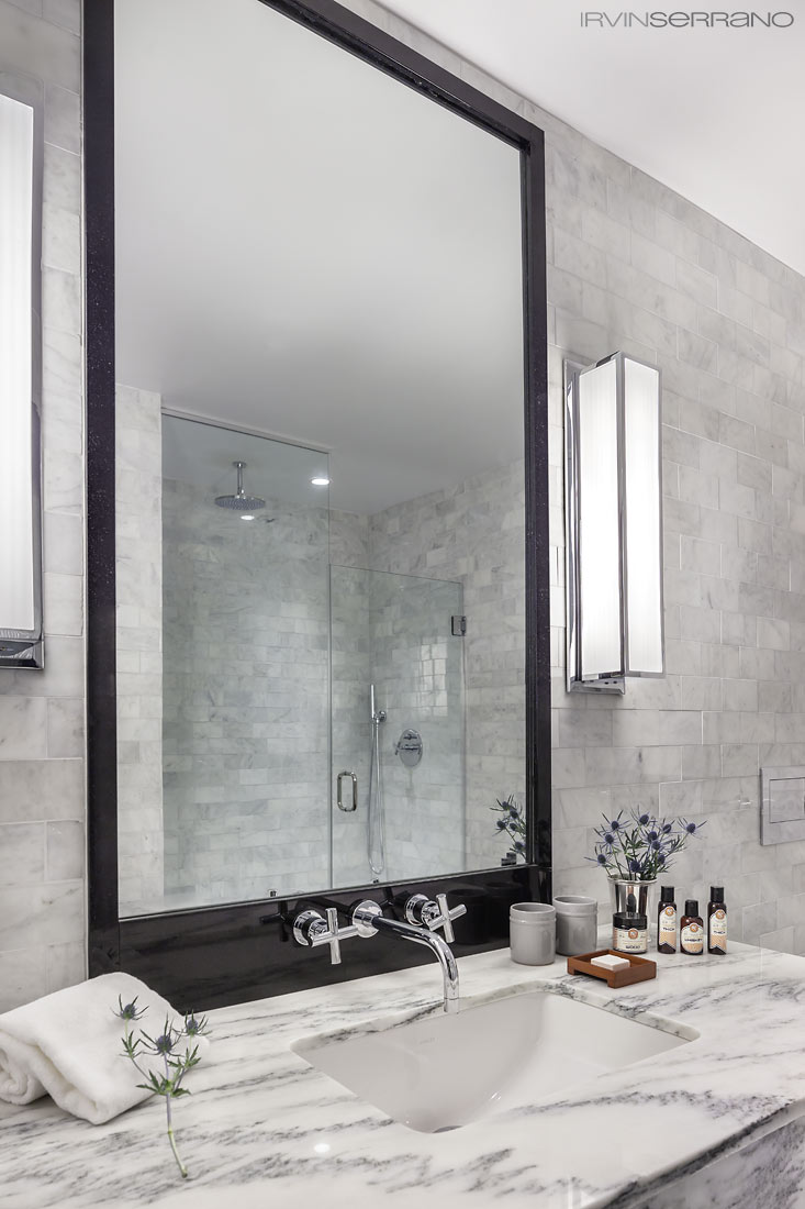 Marble-tiled bathrooms with rain head shower by Kohler and C.O. Bigelow Apothecaries adorn Press Hotel bathrooms.