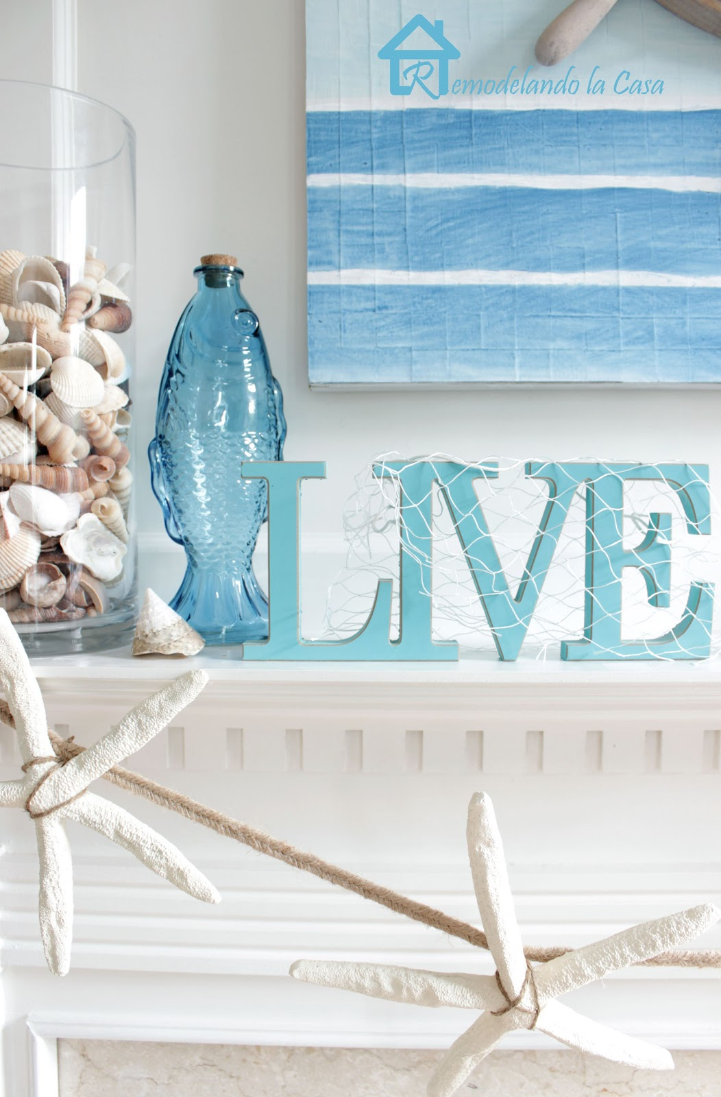 mantel with seashells and ship-wheel art