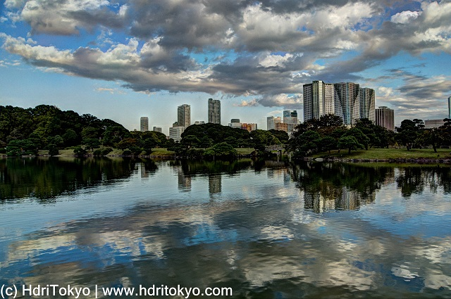 pond and white cloud with reflection on water. skyline of Shiodome district in background
