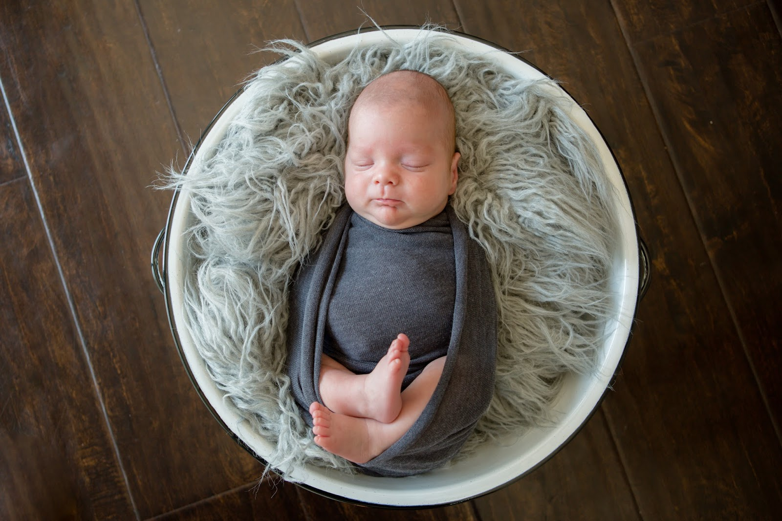 newborn baby born swaddled in gray swaddle