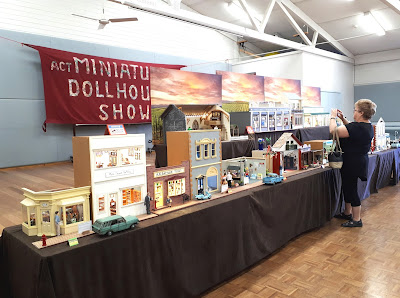 A woman photographing one of the one-twelfth scale buildings on display at a miniatures show. Behind the display hangs a fabric wallhanging that spells out 'ACT Miniature and Dollshouse show'.