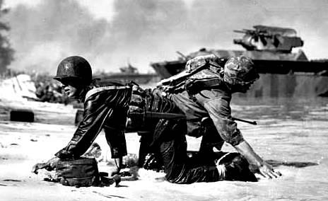 Marines de los EEUU que vienen a tierra bajo fuego japonés en Saipan