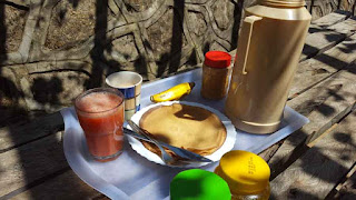 picture of a tray of food with juice, milk, tea, a banana, and nut butter