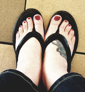 image of my feet in black flip-flops with my toenails painted dark red
