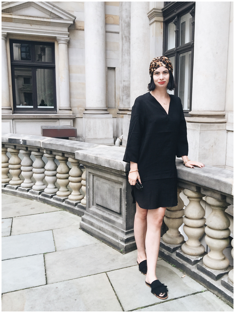 BLACK LEOPARD | June Gold wearing a black H&M dress, black & other stories fringed slip on sandals and a leopard printed topshop turban