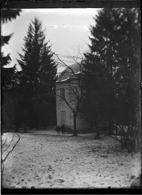 Foto von zwei Personen vor einem Haus, eine davon mit Fotoapparat auf Stativ - um 1900