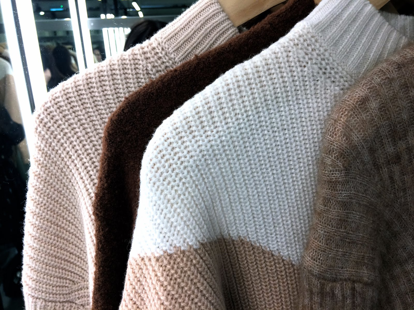 Collection of beige coloured jumpers hanging next to each other