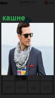 Мужчина в очках и пиджаке, у которого вокруг шеи повязано кашне