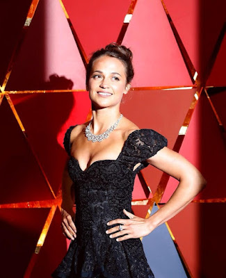 Alicia Vikander posing for her necklace From Her Jewelry Display Collection.