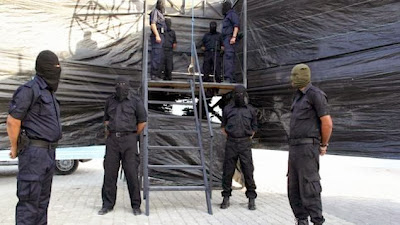 Hamas militants carrying out an execution in Gaza City in October 2013
