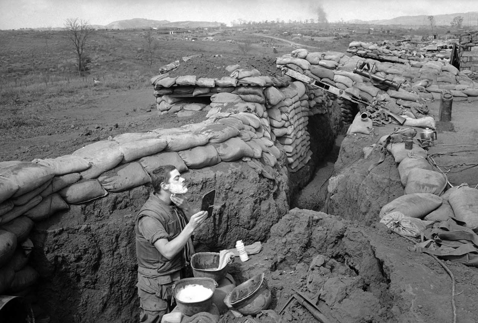 Marine Lance Corporal Roland Ball of Tacoma, Washington, wearing his flak vest, starts the day off with a shave in a trench at the Khe Sanh Base in Vietnam on March 5, 1968, which was surrounded by North Vietnamese regulars. Ball uses a helmet as a sink and a rear-view mirror taken from a military vehicle.