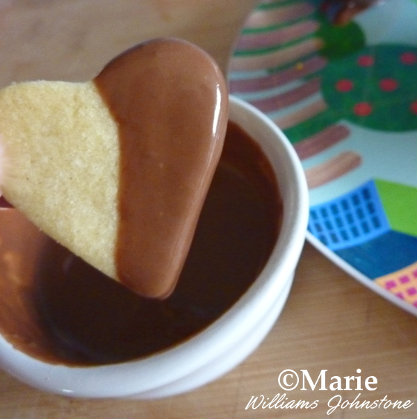 Dipping the Heart Shaped Cookies into Melted Chocolate