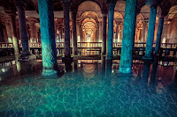 İçinde kemerli sütunlar ve dibinde mavi bir su olan İstanbul Yerebatan Sarnıcının bir fotoğrafı