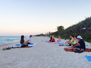 Group sitting on beach doing beach yoga