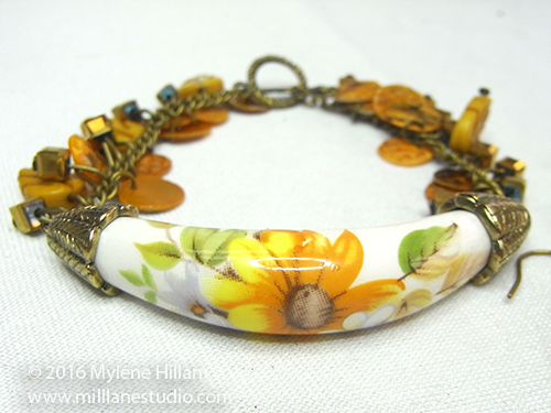 Sunshine and Happiness bracelet featuring a curved ceramic bead with yellow daisy decal, and a chain of dangling yellow beads.