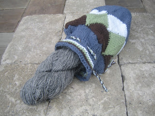 An image of a knitted bag, made up of mitered squares knitted in four colours.  It is laying flat, and open.  The top has eyelets and a drawstring cord.