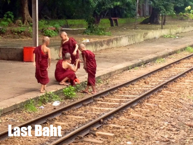 four red-robed novice monk children play by the train tracks in Burma (myanmar) countryside