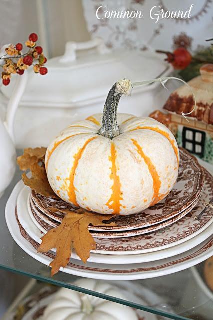 cupboard full of transferware, pumpkins, leaves,