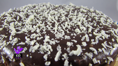 side view to see the white chocolate on top of the chocolate covered, chocolate cheesecake on a chocolate crust