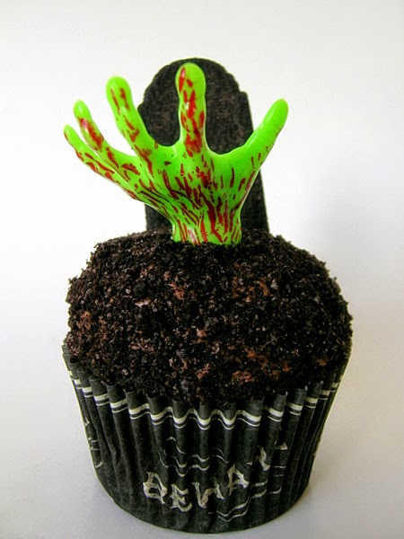Chocolate frosted cupcake in black and white case with green hand and tombstone decoration