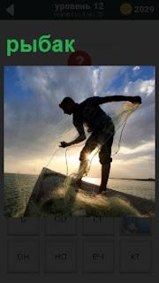 Мужчина вытаскивает из воды сеть для ловли рыбы, наклонившись близко к воде