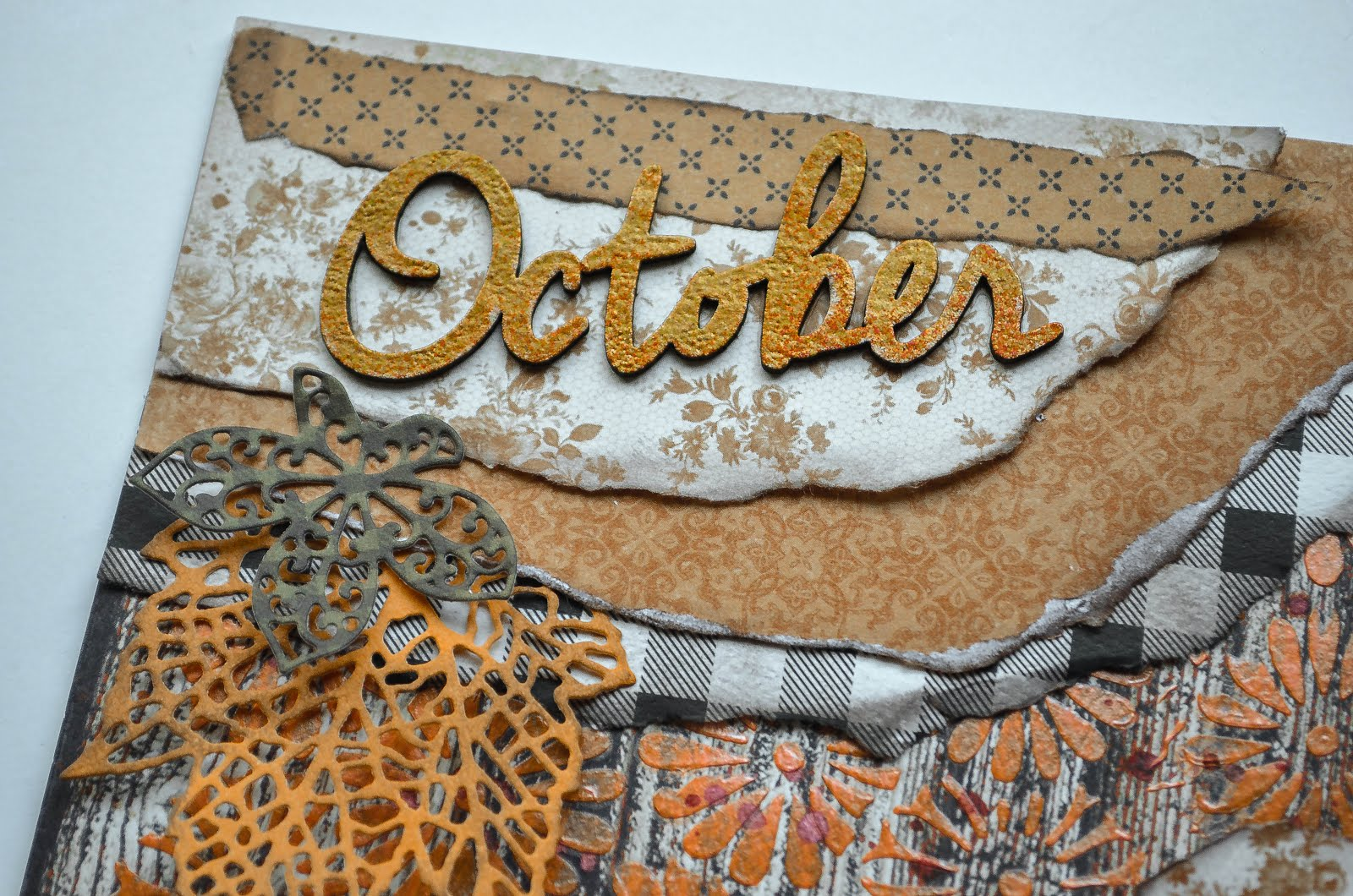 October autumn fall scrapbook layout on in orange, brown, and black on wood grain background with flowers by Kaisercraft and Petaloo, with background stenciling with Dreamsicle texture paste, torn paper layers, and Prima die cut leaves  with chipboard by Creative Embellishments
